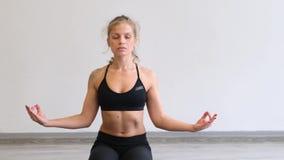 Ung kvinna som gör yoga på idrottshallen Vit bakgrund 4K arkivfilmer