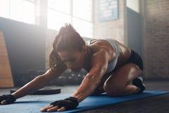 Ung kvinna som gör yoga på idrottshallgolvet royaltyfri fotografi