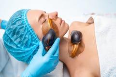 Ung kvinna som genomgår behandling med jätteAchatina sniglar i skönhetsalong royaltyfri foto