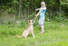 Ung kvinna som ger kommandon till hennes hund, medan gå på stranden royaltyfria foton