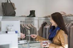 Ung kvinna som ger kreditkorten till kassörskan Royaltyfri Fotografi