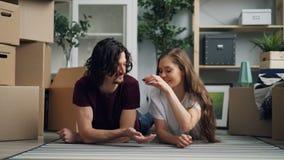 Ung kvinna som ger tangent till maken som kysser därefter på golv i ny lägenhet arkivfilmer