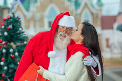 Ung kvinna som ger till santa en kyss Royaltyfria Foton