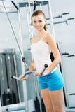 Ung kvinna som gör bodybuilding i idrottshallen Arkivbild