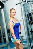 Ung kvinna som gör bodybuilding i idrottshallen Arkivbilder