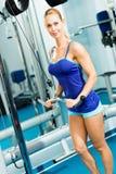 Ung kvinna som gör bodybuilding i idrottshallen Royaltyfri Fotografi