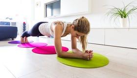 Ung kvinna som gör liggande armhävningar i hennes vardagsrum Arkivfoto