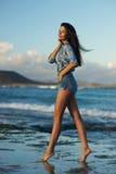 Ung kvinna som går på stranden Arkivfoto