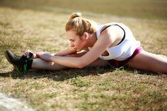 Ung kvinna som gör sträcka övningen, genomkörare på gräs Royaltyfri Bild