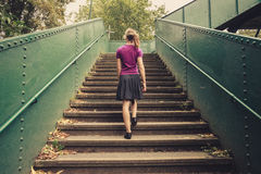 Ung kvinna som går upp trappa Royaltyfria Bilder