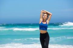 Ung kvinna som går vid stranden med lyftta armar Arkivfoton