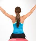 Ung kvinna som gör övningar på övningsboll Arkivbild
