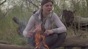 Ung kvinna som grillar marshmallower stock video