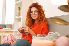Ung kvinna som grinar, medan sticka halsduken arkivbild