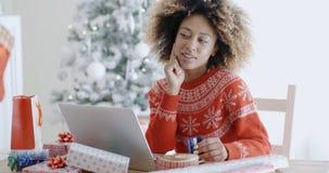 Ung kvinna som grubblar över ett online-köp Arkivfoto