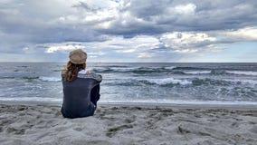 Ung kvinna som hänsynsfullt sitter vid havet med stormig himmel, blickar på horisonten fotografering för bildbyråer