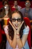 Ung kvinna som håller ögonen på en film 3d Arkivbild