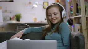 Ung kvinna som håller ögonen på en TV-program på bärbara datorn, i hörlurar och att le arkivfilmer