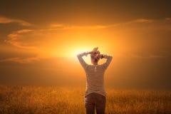 Ung kvinna som håller ögonen på solnedgången Arkivfoto