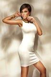 Ung kvinna som ha på sig den trendiga vitklänningen Royaltyfria Bilder