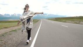 Ung kvinna som hake-fotvandrar på en väg på fälten arkivfilmer