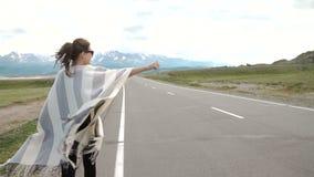 Ung kvinna som hake-fotvandrar på en väg på fälten stock video