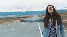 Ung kvinna som hake-fotvandrar på en väg på fälten Hippy lifta för ung flicka på vägen Bland bergen in lager videofilmer