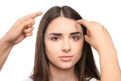 Ung kvinna som har ögonbrynkorrigeringstillvägagångssätt royaltyfria foton