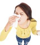 Ung kvinna som har allergi och blåser in i silkespapper Fotografering för Bildbyråer