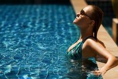 Ung kvinna som har bra tid i simning Arkivfoto