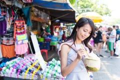Ung kvinna som har den saftiga kokosnöten i gatamarknad Royaltyfri Fotografi