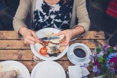 Ung kvinna som har en engelsk frukost arkivfoton