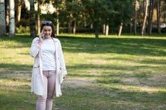 Ung kvinna som har en konversation på hennes smartphone royaltyfri foto