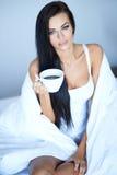 Ung kvinna som har en morgonkopp kaffe royaltyfria foton
