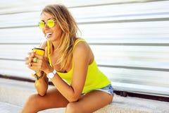 Ung kvinna som har en uppfriskande drink för sommar utanför härligt royaltyfri foto
