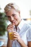 Ung kvinna som har exponeringsglas av orange fruktsaft Arkivfoton