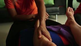Ung kvinna som har fotmassage i skönhetbrunnsortsalong ben för närbildkvinna` s och händer för massör` s lager videofilmer
