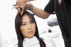 Ung kvinna som har frisyr på skönhetsalongen fotografering för bildbyråer