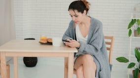 Ung kvinna som har frukosten i kök och bläddrar internet, genom att använda smartphonen Flickan äter gifflet, dricker kaffe Royaltyfri Bild