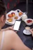 Ung kvinna som har frukosten, medan genom att använda smartphonen royaltyfri bild