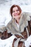 Ung kvinna som har gyckel med snö på vinterdag Arkivfoton