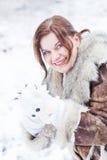 Ung kvinna som har gyckel med snö på vinterdag Arkivfoto