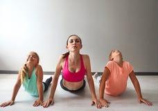 Ung kvinna som har gyckel med ungar som gör yoga arkivbild