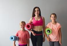 Ung kvinna som har gyckel med ungar som gör yoga arkivfoto