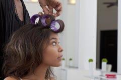 Ung kvinna som har hår att krullas i skönhetsalong arkivfoto