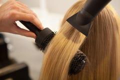 Ung kvinna som har hennes hår att utformas av frisören royaltyfria bilder