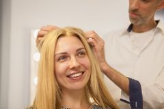 Ung kvinna som har hennes hår att utformas av frisören arkivbilder