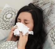 Ung kvinna som har influensa som blåser hennes näsa Arkivbilder