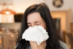 Ung kvinna som har influensa som blåser hennes näsa Arkivfoton