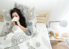 Ung kvinna som har influensa som blåser hennes näsa Royaltyfri Fotografi